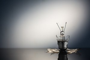 Shattered light bulb standing with copy space