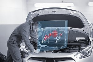 Man repairing car with open hood and futuristic interface