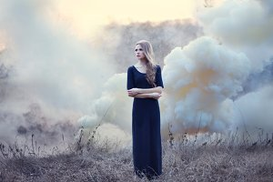 girl in smoke on nature on sunset