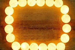Lights frame on wooden background