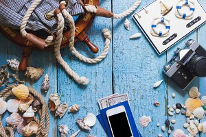 Striped bag, wheel, phone and maritime decorations on the wooden background