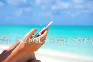 Young woman use phone during tropical beach vacation. Closeup mobile smartphone.