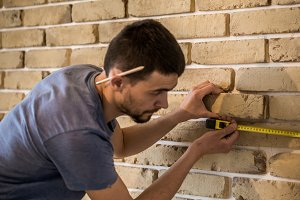 male works with brick wall with centimeter
