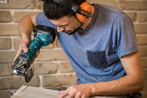 man in headphones works with manual electric saw