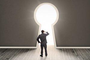 Businessman looking through a keyhole shape door
