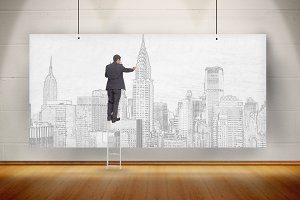 Businessman standing on ladder and drawing a city on a poster hung