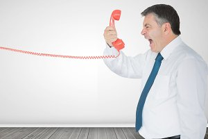 Businessman holding a phone and screaming