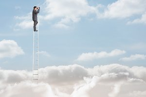 Businessman standing on a ladder over the clouds