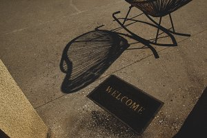 The shadow from the wicker chair and the rug with the inscription Welcome