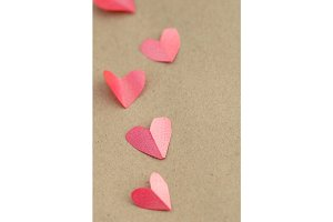 Paper hearts on a craft paper background.