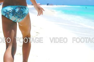 Little girl running on the white beach in shallow water. Concept of beach vacation and barefoot. SLOW MOTION