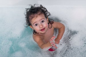 cute little girl bathes in a bathtub, the concept of hygiene and cleanliness