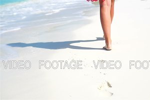 Female legs running along the white beach in shallow water. Concept of beach vacation and barefoot. SLOW MOTION.