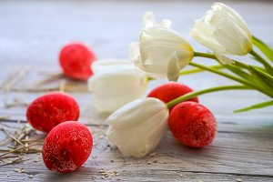 White tulips and red Easter eggs