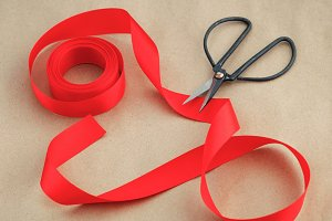 Preparing for the packaging of gifts. Black vintage scissors and red silk ribbon on kraft paper. View from above.