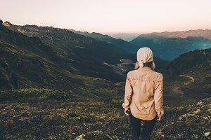 Woman hiking at sunset mountains