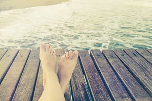 Summer holidays concept background with legs over wooden pier