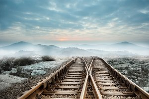 Railway tracks leading to mountains