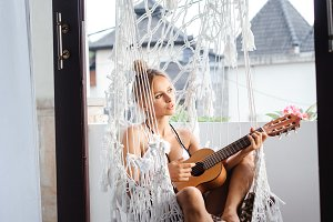 woman playing ukulele in hammock
