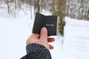 Discover or Joyrney concept. Hand holding a book with the inscription. On the background of the winter forest