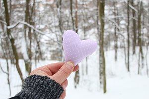 Hand holding a heart on the background of the winter forest