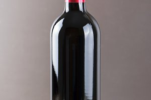 Red wine bottle on wooden background. Vetical studio shot.
