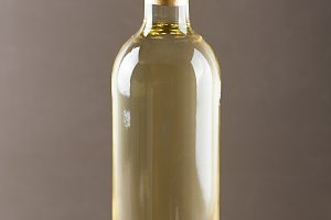Vertical studio shot of bottle of white wine on the wooden background.