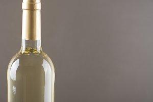 White wine bottle on gray background Horizontal studio shot. Copy space.
