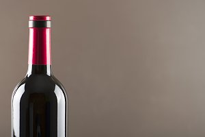 Red wine bottle on gray background Horizontal studio shot. Copy space.