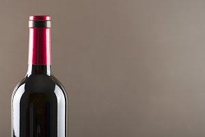 Red wine bottle on gray background Horizontal studio shot. Copy space.