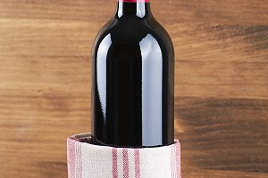 Close-up of red wine bottle with a napkin placed on wooden table. Horizontal studio shot. Copy space.