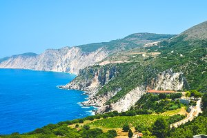 Cephalonia shore cliffs and blue coastal sea waters. Olive plantage in foreground