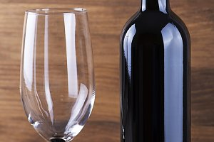Red wine bottle and a glass placed on wooden table. Copy space. Vertical studio shot