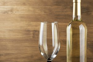 White wine bottle and a glass placed on wooden table. Copy space. Horizontal studio shot. Copy space.