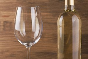 White wine bottle and a glass placed on wooden table. Copy space. Vertical studio shot