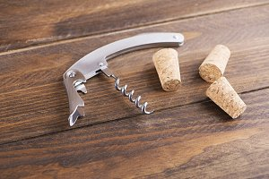 Close-up of corkscrew next to several corks. Horizontal studio shot.