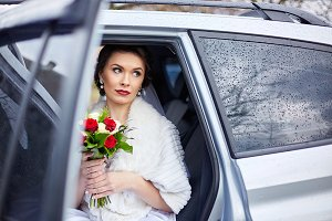 Beautiful bride sits in white car