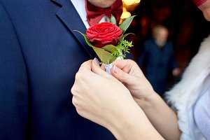Bride pins red rose boutonniere