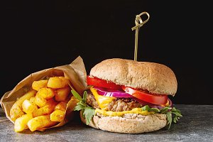 Fast food. Not a diet. Homemade vegetarian burger with rocket salad, cheese, chicken, sauce and fries. Dark background.