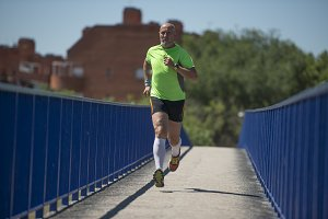Senior retired man runs and performs exercise