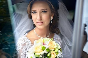 Pretty bride sits in the car