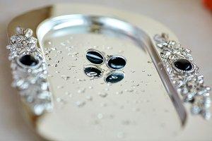 Black earrings lie on silver tray