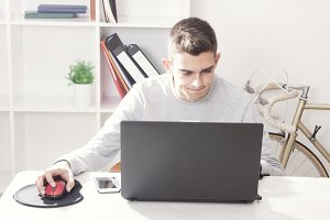 young man with the computer in the room working