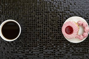 Cup of black coffee with pink donuts