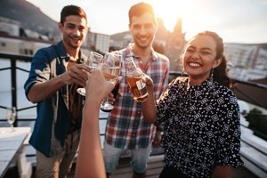 Friends toasting drinks on a rooftop