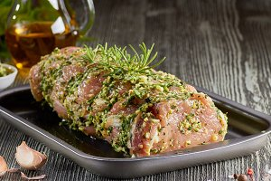 Raw pork loin with spices in baking tray.