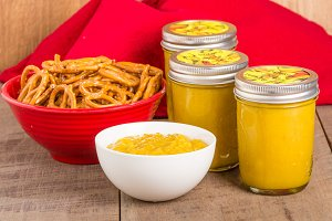 Jars of homemade mustard with pretzels