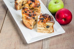 Baked apple bread pudding on white plate