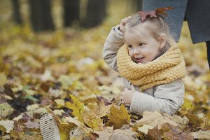 Little blonde baby girl plays with leaves in autumn park