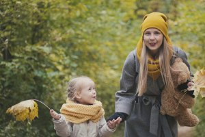Blonde woman with little daughter in autumn park